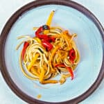 bucatini pasta with roasted peppers in olive oil on a round plate