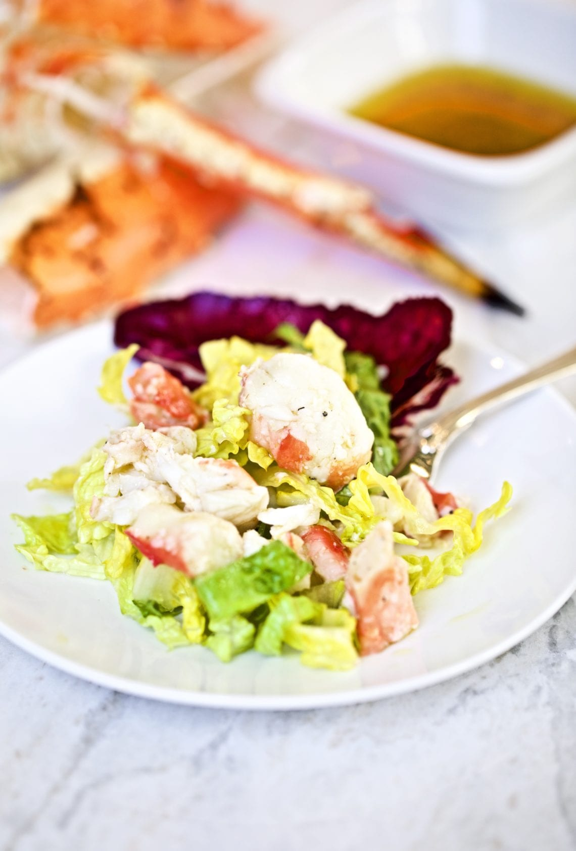 king crab on a plate with lettuce and cup of salad dressing