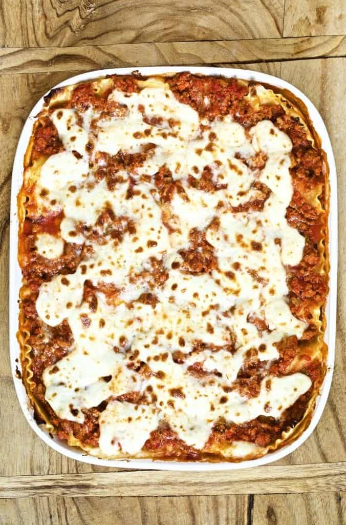 A huge pan of lasagna with cheese on top. Red layers of sauce and delicious cheese
