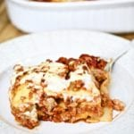 piece of square lasagna on a plate with a large lasagna pan in the background