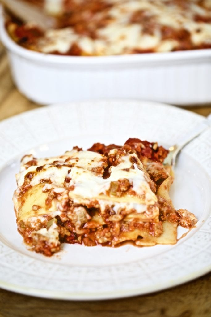 final piece of lasagna on a plate with a fork ready to eat