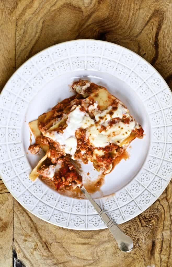 slice of lasagna on a white plate with a fork ready to eat it