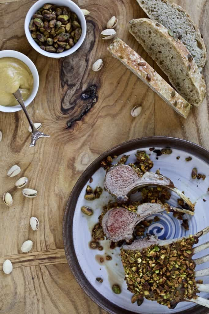 Roasted leg of lamb on a plate sitting on a wooden board with pistachios as decoration