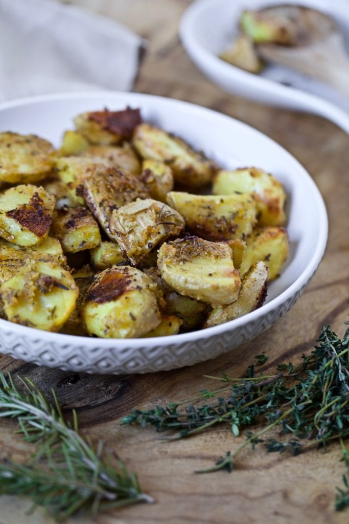 oven roasted potatoes with a crispy exterior and herbs placed in a white bowl on a wooden board