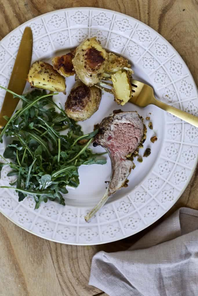 final dish with roasted rack of lamb, salad, and potatoes on a plate