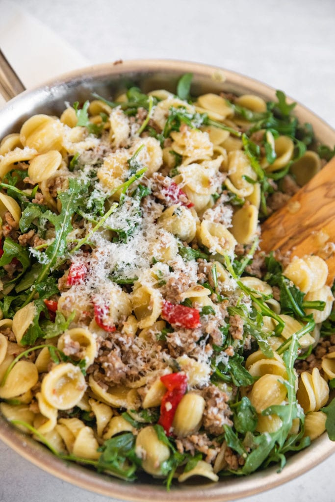 platted final dish of pasta and sausage with arugula and red peppers in a pan with wooden spoon