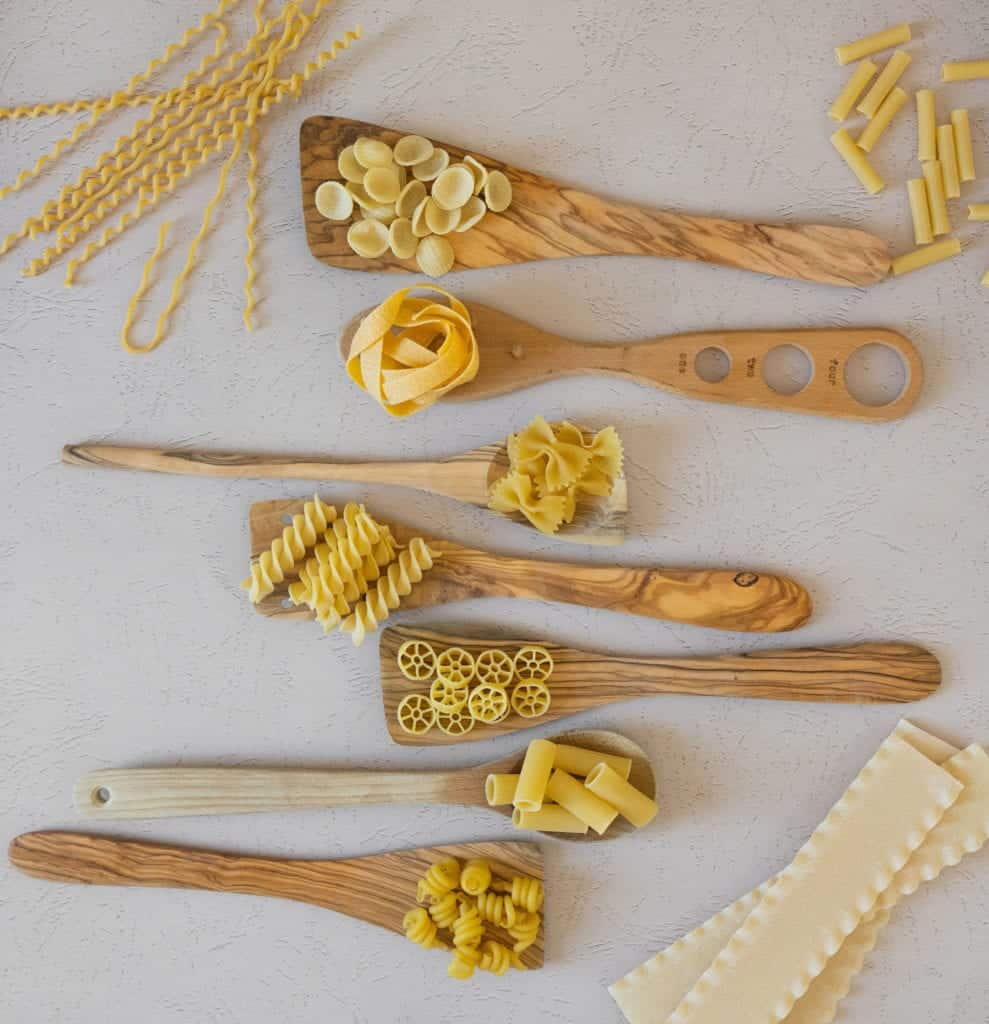 different pasta shapes with wooden spoons