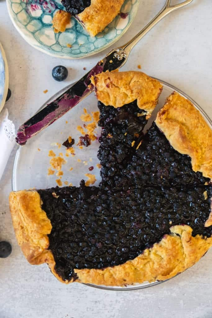 blueberry galette cut with a slice taken out and flaky pastry crust