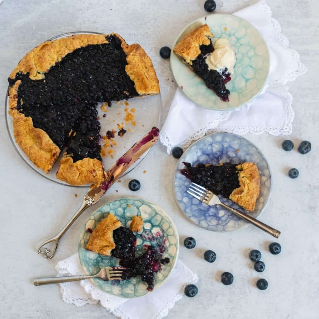 blueberry galette cut in pieces on pretty plates with ice cream