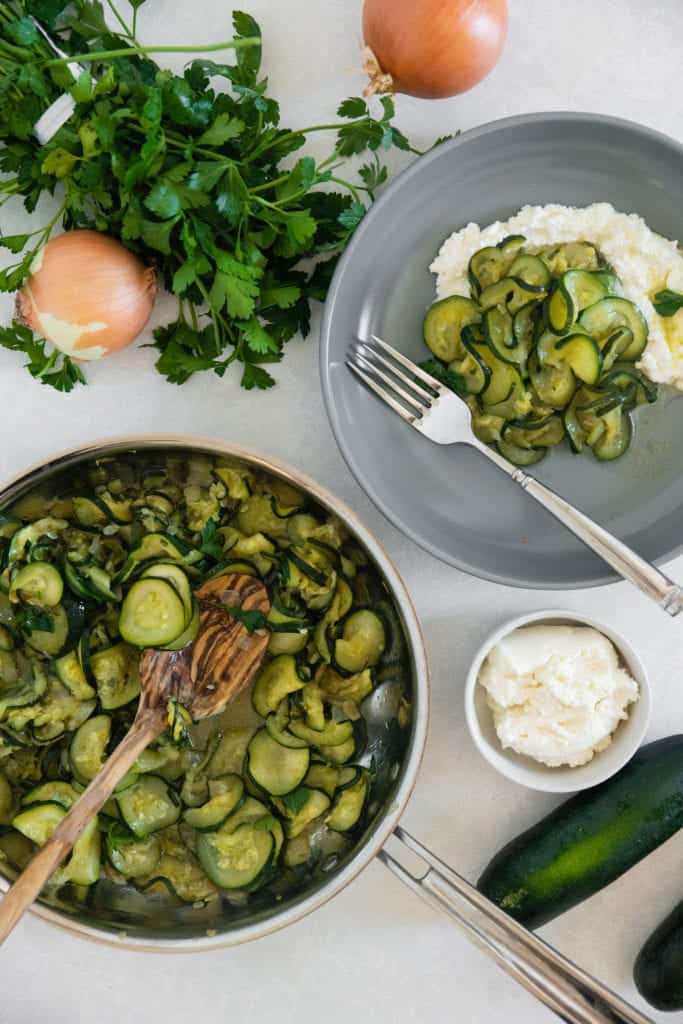 fresh onions and zucchini with a bowl of ricotta to show the ingredients in this dish