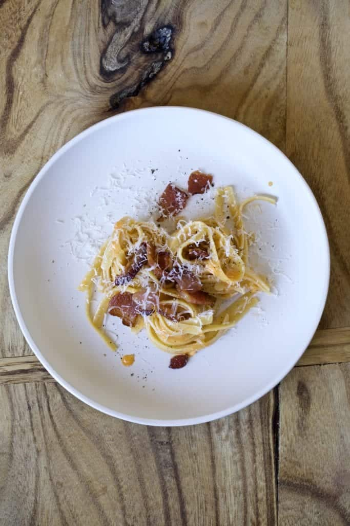 carbonara on a plate with wooden board