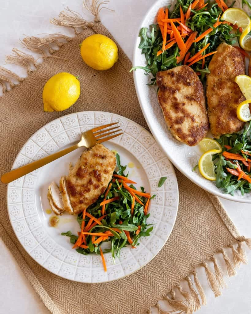 breaded chicken fried on a skillet served with salad on a plate and lemons