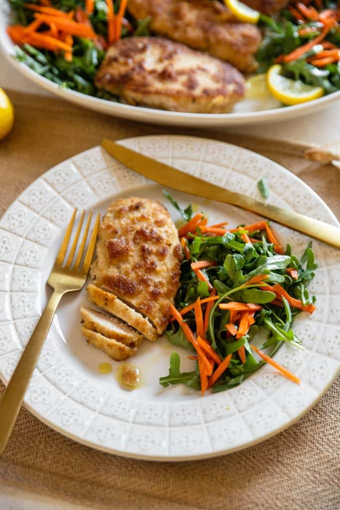 pan fried chicken breast on a plate with salad and carrots