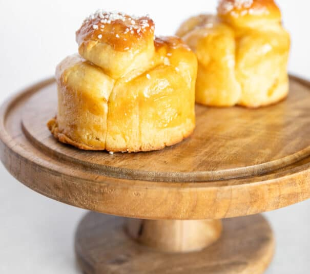 brioche buns on a wooden cake stand
