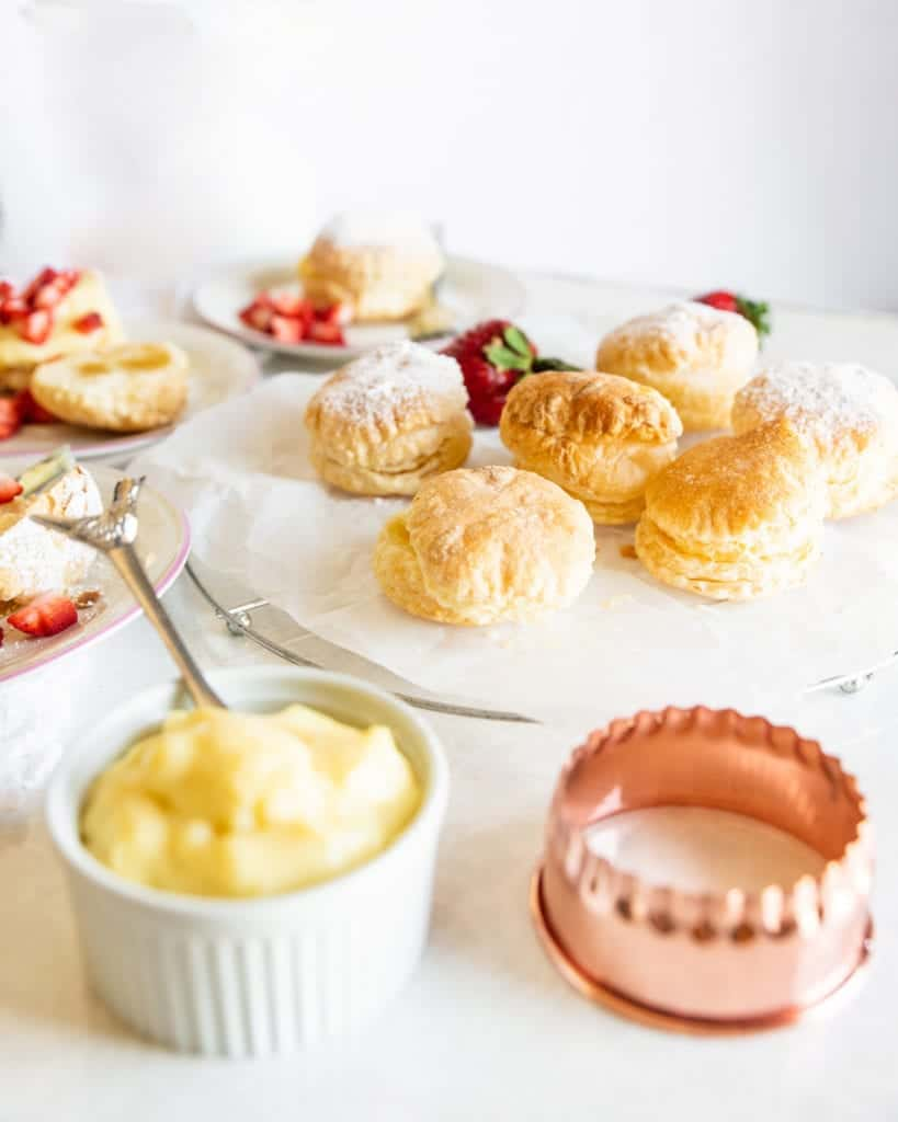 puff pastries filled with cream on a plate with strawberries