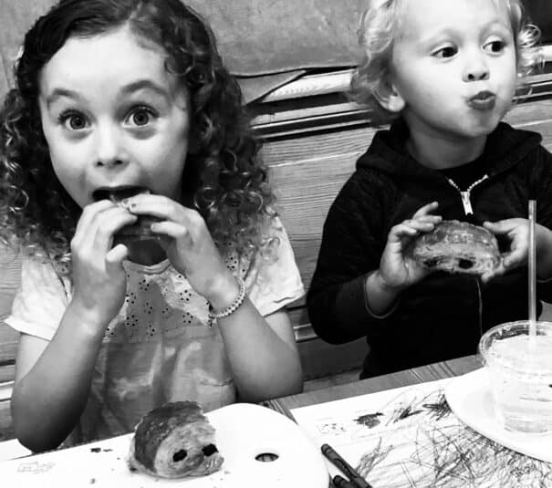two kids eating a chocolate croissant