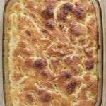 Italian Focaccia Bread in a pan and a wooden board