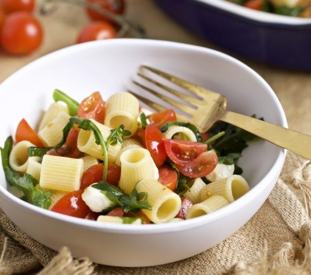 pasta salad with arugula, tomatoes, mozarella in a bowl
