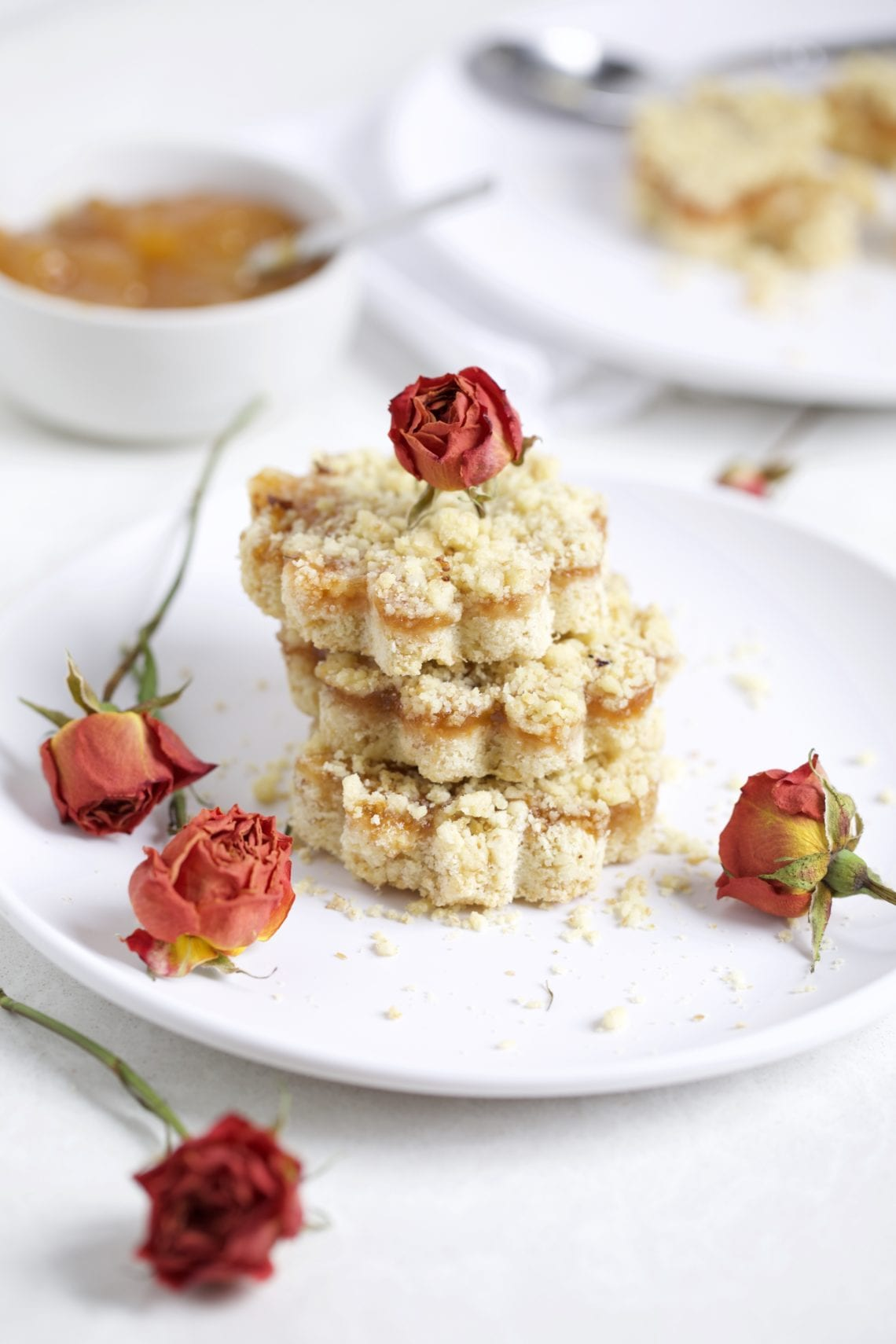 Italian Crumb cake with jam on a plate with dried roses