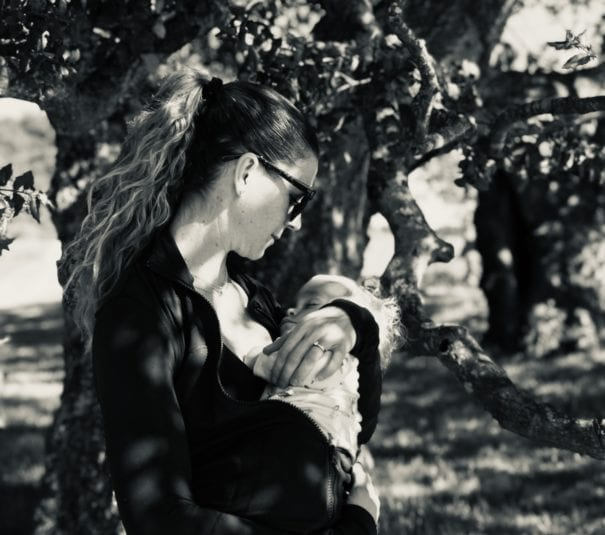 mother holding a baby in a forest. Black and white photo
