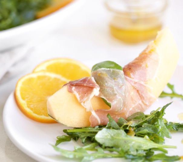 Cantaloupe Melon on plate wrapped in prosciutto with citrus vinaigrette