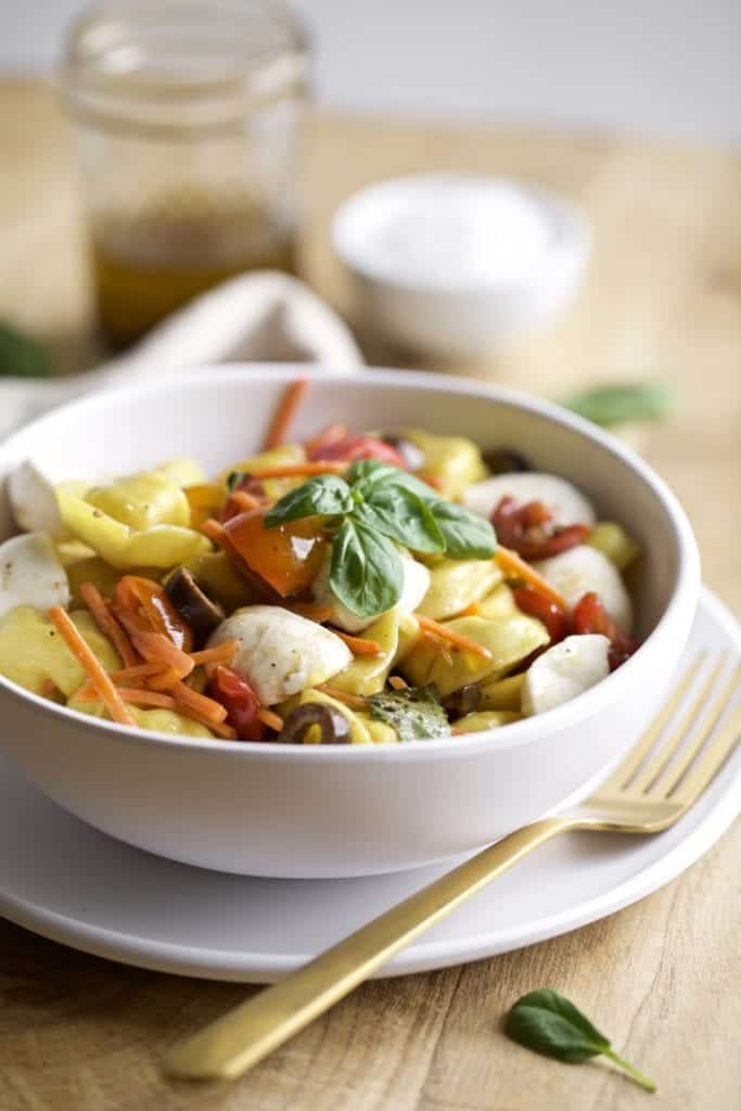 pasta salad in a bowl with cheese and vegetables