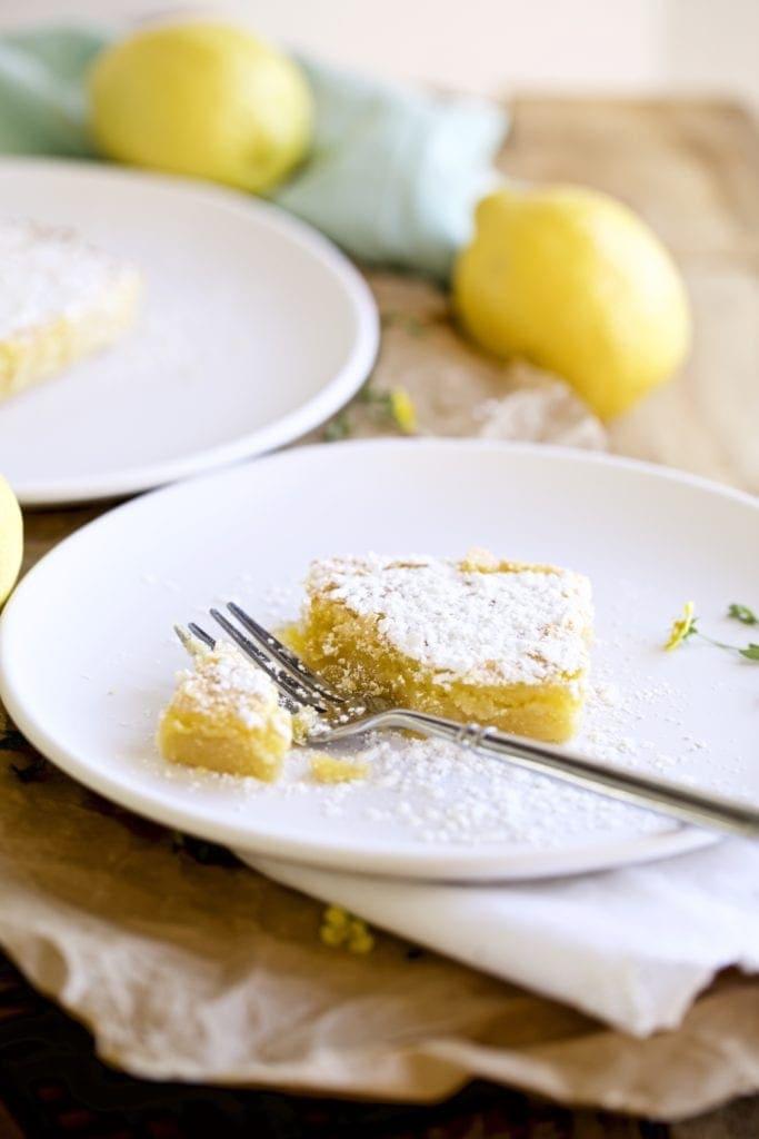 lemon bar on a plate with a fork